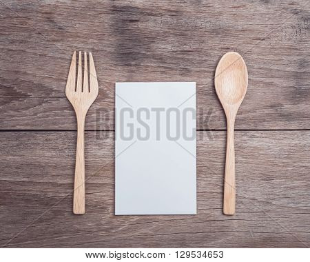Wooden Spoon, Fork And Blank Paper On Wooden Table Top View