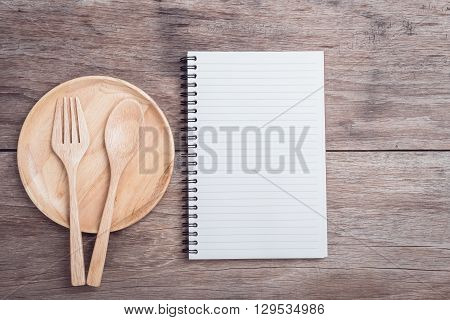 Wooden Dish, Spoon, Fork And Lined Paper On Wooden Table Top View