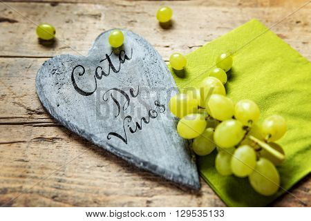 White grapes on wooden table wooden heart with spanish text Cata de vinos on it which means wine festival