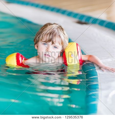 Portrait of little blond kid boy with swimmies  in an indoor swimming pool. Active and fit leisure for children.