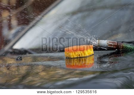 Sprinkling water hose and a colorful sponge laid on the car hood outdoor selective focus shot