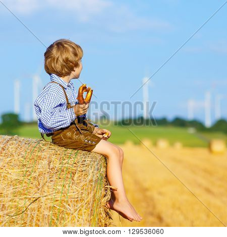 Adorable little kid boy sitting on hay stack or bale and eating traditional pretzel. Child in bavarian clothes