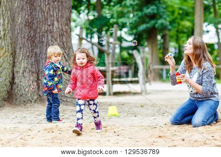 Happy mother and two little children playing together on playground in summer. Funny toddler boy and girl, siblings having fun together