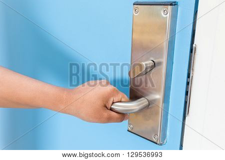 Hand Holding On Stainless Steel Door Handle In Hotel