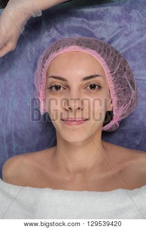Closeup Girl is before the Procedure Facial Mask in Beauty salon. Spa Woman before applying Facial clay Mask. Beauty Treatments. Beautiful girl in cap on her head before applying facial mask.