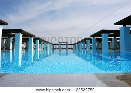 HERAKLION, CRETE, GREECE - MAY 13, 2014: The big blue swimming-pool modern building with columns and beach in popular luxury class hotel on the Mediterranean coast of Crete, May 13, 2014, Greece.