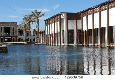 HERAKLION, CRETE, GREECE - MAY 13, 2014: The big blue swimming-pool modern building with columns palms in popular luxury class hotel on the Mediterranean coast of Crete, May 13, 2014, Greece.