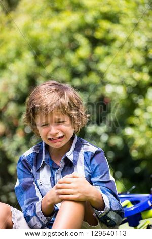 Portrait of cute boy crying cause of his bike fall on a park