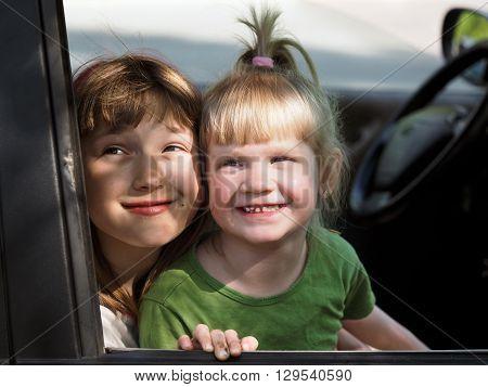 Children look out the car window. Children grimy, satisfied. Portrait of two girls. Concept - travel with children in the car. Children's holiday, happy children.