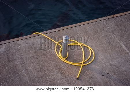 Dock post with a yellow line at a harbor