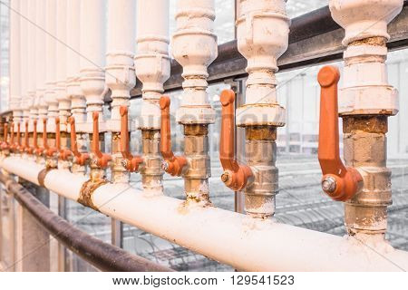 Orange handles on white pipes at a factory