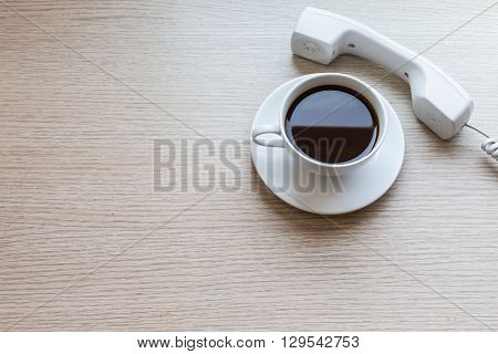 White Coffee Cup And Office Phone On Wooden Table