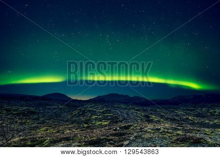 Northern Lights Over Distant Mountains