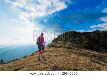 Slender Woman Practicing Nordic Walking In The Mountains