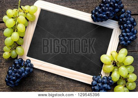 White and blue grapes and a slate with copyspace on wooden table