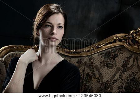 Portrait of beautiful young woman sitting on sofa, looking away.