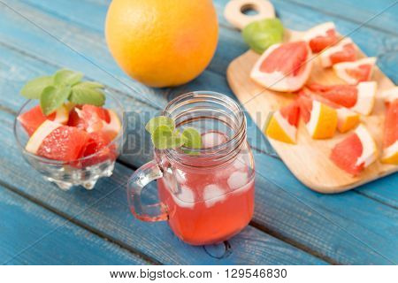 Freshly squeezed orange and grapefruit juice in glass with fruits on wooden background