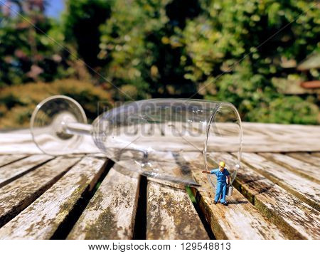 Miniature Workman Collecting Water Or Wine With Jerrycan From Fallen Champagne Glass
