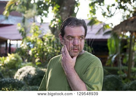 Pensive mature man in the yard of his house