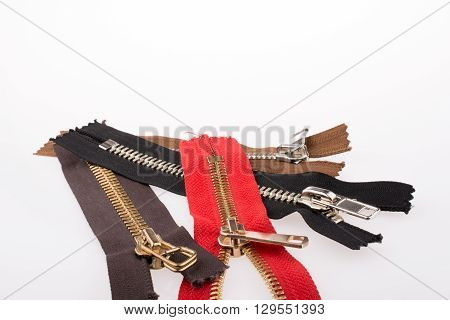 zippers of various color on  a white background