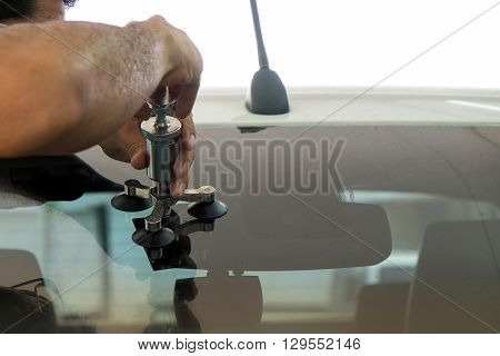A Man Using Repairing Equipment To Fix Damaged Windshield