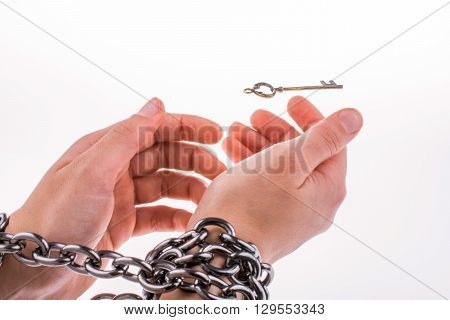 Both chained hands and the key on white background