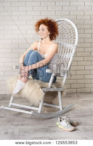 Portrait Of The Young Beautiful Girl Sitting In A Rocking-chair Against A Brick Wall