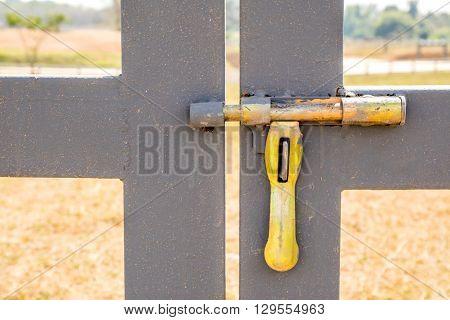 Grunge yellow bolt of entrance door in Farmland.