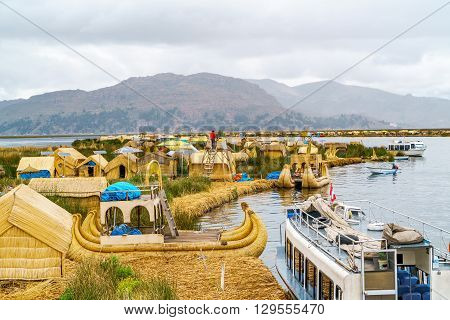 View at the Floating Island Los Uros with typical boats in Lake Titicaca Puno Peru