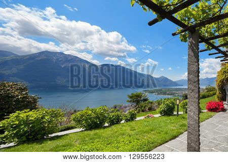 beautiful garden with pergola of a villa, lake view