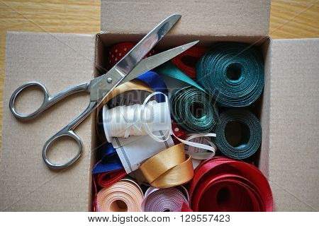 Cardboard box full of equipment for sewing, stitching  and for decorating  of gifts and presents