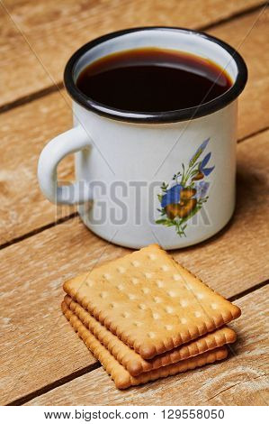 Metal cup with coffee and cookies on planked wooden table
