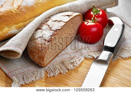 Sliced loaf of gray floured bread, tomatoes and knife on cotton towel on wooden cutting board