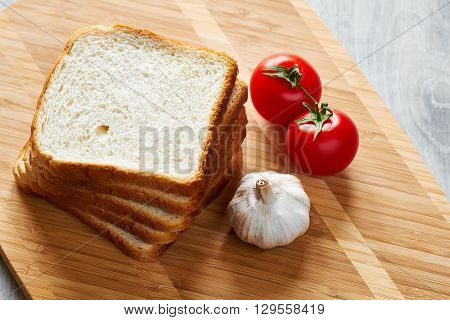 Slices of bread for toasting, tomatoes and garlic on cutting board