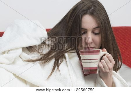 Sick teenager girl wearing bathrobe with fever drinking tea