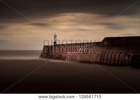 Normally photographed during raging storms, Porthcawl lighthouse shown in a calm mood by using a ten stop filter