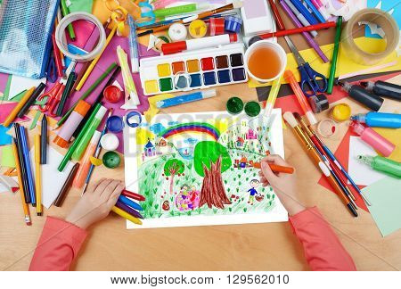 people relax on meadow near the village, child drawing, top view hands with pencil painting picture on paper, artwork workplace