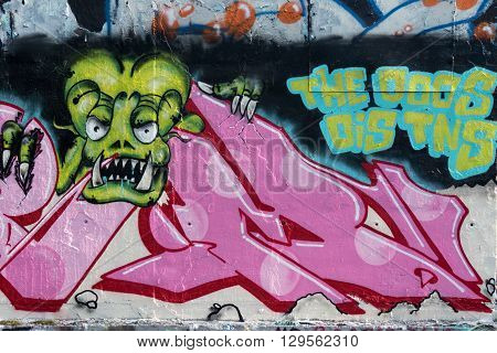 Wall painted grafitti, pink with green monster alien