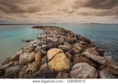 The breakwater at San Pedro Beach in Betlem, Mallorca, looking over Alcudia Bay towards Cap des Pinar and Cap de Formentor.