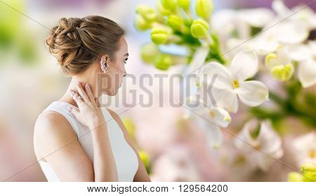 glamour, beauty, jewelry and luxury concept - close up of beautiful woman with golden ring and diamond earring over natural spring lilac blossom background