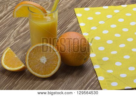 Orange juice in glass,  fresh fruits on brown wooden background