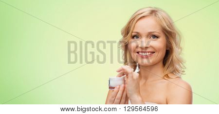beauty, people, skincare and cosmetics concept - happy woman with cream jar over green natural background