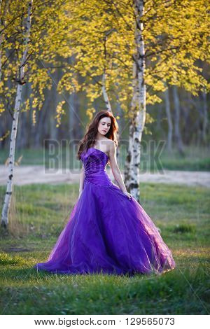 Attractive girl dressed evening gown under the birch