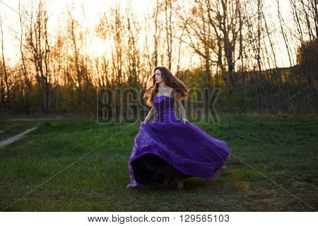 Running attractive girl dressed evening gown at sunset