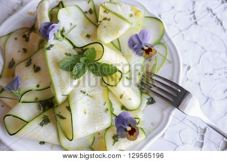 Edible flowers and Zucchini courgette salad with mint lemon dressingselective focus