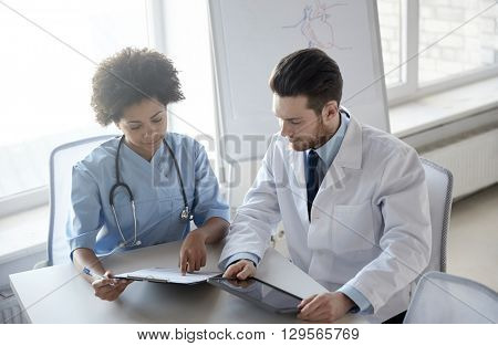 health care, people, technology and medicine concept - doctor and nurse with tablet pc computer and clipboard meeting and discussing something at hospital