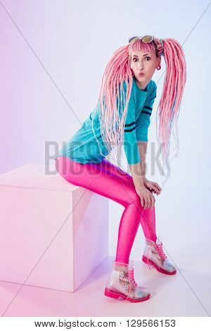 Modern teenage girl with pink dreadlocks on white background