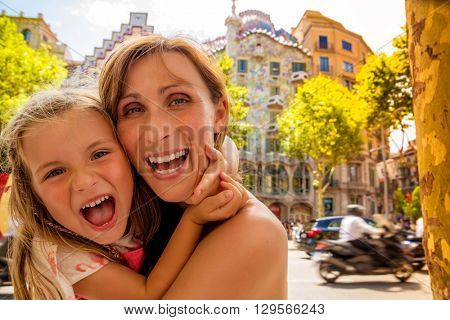 mother with daughter visiting barcelona rambla with gaudi house background