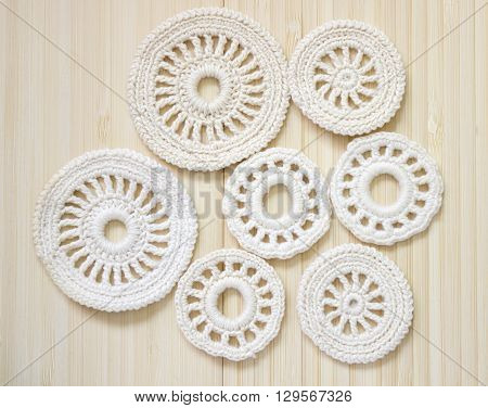 White vintage elements of Irish crochet. Cotton yarn for knitting crochet. Crochet doilies crochet pattern coasters on bamboo background