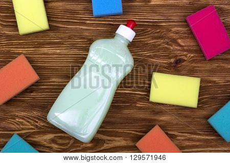 sponges and a bottle of detergent on wooden background